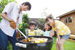 庭でバーベキューをする家族の写真素材 [FYI02022619]