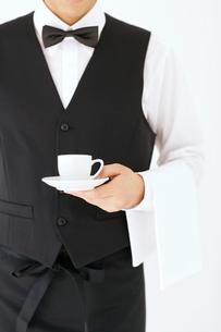 コーヒーカップを持つウェイターの写真素材 [FYI02022625]