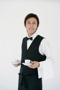 コーヒーを運ぶフロアスタッフの写真素材 [FYI02022801]