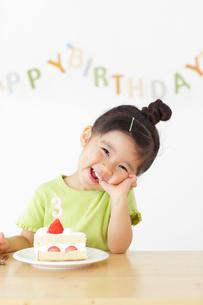 バースデーケーキを前に喜ぶ女の子の写真素材 [FYI02023047]