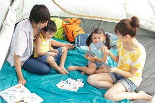 テントの中でトランプをする家族の写真素材 [FYI02023097]