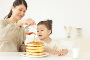 パンケーキにシロップをかける母と見つめる娘の写真素材 [FYI02023162]