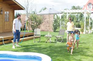庭でシャワーの水遊びをする親子の写真素材 [FYI02023206]