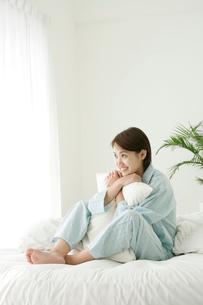 ベッドの上で寛ぐ女性の写真素材 [FYI02023374]