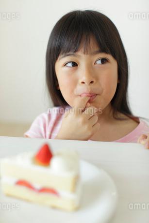 ケーキの生クリームを舐める女の子の写真素材 [FYI02023394]