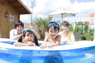 プールに入る子供と見守る両親の写真素材 [FYI02023408]