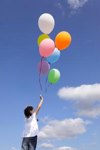 青空の下カラフルな風船を飛ばす女の子の写真素材 [FYI02023499]