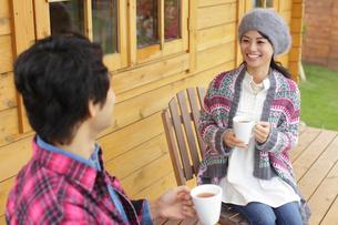 ログハウスの前でコーヒーを飲むカップルの写真素材 [FYI02023512]