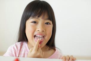 ケーキの生クリームを舐める女の子の写真素材 [FYI02023553]