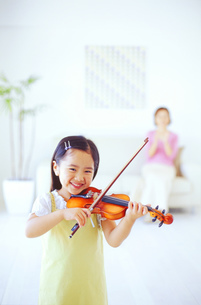 バイオリンを弾く女の子と見守る母の写真素材 [FYI02023873]