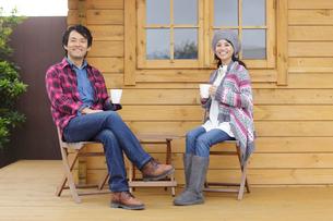 ログハウスの前でコーヒーを飲むカップルの写真素材 [FYI02023942]