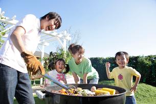 庭でバーベキューを楽しむ家族の写真素材 [FYI02024091]