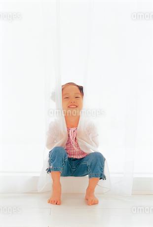 カーテンで遊ぶ女の子の写真素材 [FYI02024151]