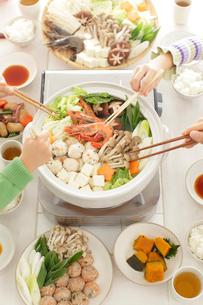 家族で鍋をつつく様子の写真素材 [FYI02024183]
