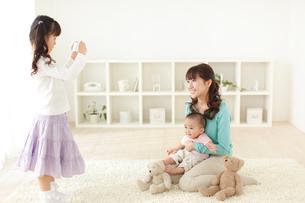 お母さんと赤ちゃんの写真を撮る女の子の写真素材 [FYI02024252]