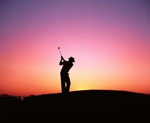 夕陽の中のゴルファーのシルエットの写真素材 [FYI02024261]