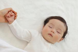 眠る赤ちゃんとお母さんの手の写真素材 [FYI02024292]