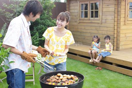 庭でバーベキューをする家族の写真素材 [FYI02024417]