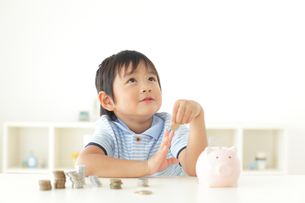 貯金箱の前で悩む男の子の写真素材 [FYI02024439]