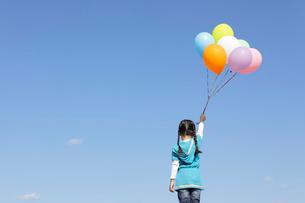 青空の下カラフルな風船を持つ女の子の後ろ姿の写真素材 [FYI02024585]