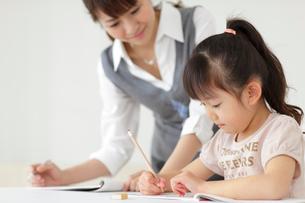先生に勉強を教わる女の子の写真素材 [FYI02024602]