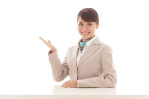 デスクに座りポーズをとる若い女性の写真素材 [FYI02024605]