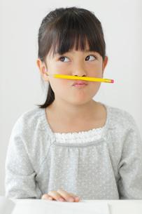 勉強中にふざける小学生の女の子の写真素材 [FYI02024702]