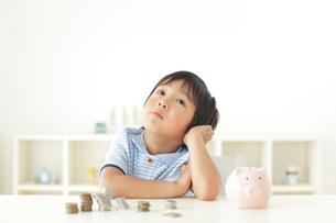貯金箱の前で悩む男の子の写真素材 [FYI02024758]