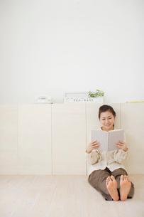 ナチュラルなリビングで本を読みくつろぐ若い女性の写真素材 [FYI02024797]