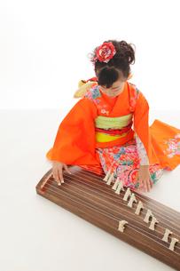振り袖を着てお琴を弾いている女の子の写真素材 [FYI02024878]