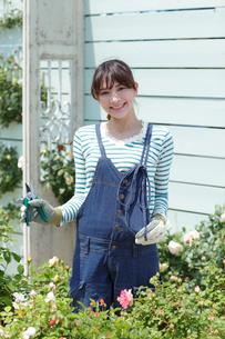 バラの咲く庭でガーデニングを楽しむ女性の写真素材 [FYI02024908]