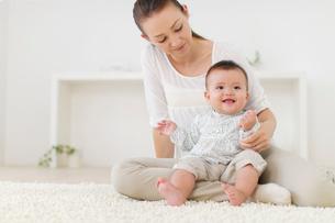 リビングでくつろぐ赤ちゃんとお母さんの写真素材 [FYI02024933]