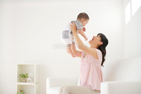リビングで赤ちゃんを抱っこするお母さんの写真素材 [FYI02025068]