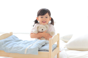 ぬいぐるみをおもちゃのベッドに寝かせて遊ぶ女の子の写真素材 [FYI02025103]