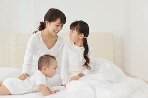 白いベッドの上のお母さんと赤ちゃんと女の子の写真素材 [FYI02025235]