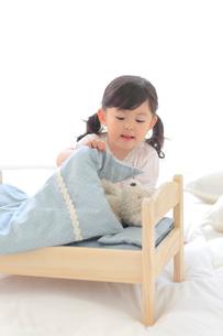 ぬいぐるみをおもちゃのベッドに寝かせて遊ぶ女の子の写真素材 [FYI02025258]