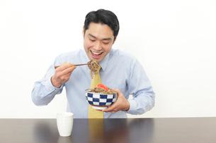 牛丼を食べるサラリーマンの写真素材 [FYI02025271]