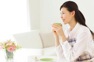 家事の合間にお茶を飲みくつろぐ若い主婦の写真素材 [FYI02025328]