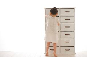 引き出しから捜し物をする女の子の写真素材 [FYI02025345]