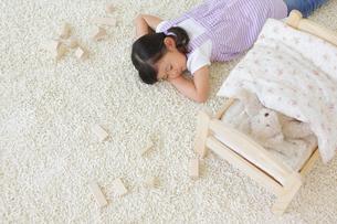 ぬいぐるみをおもちゃのベッドに寝かせてお昼寝する女の子の写真素材 [FYI02025347]