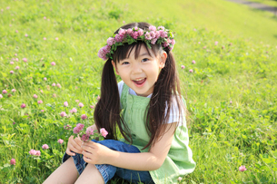 アカツメクサの花冠をかぶる女の子の写真素材 [FYI02025387]