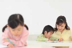 先生に勉強を習う子供達の写真素材 [FYI02025412]