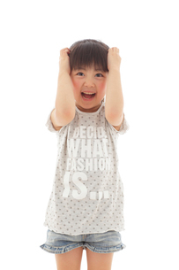 ショックを受けて頭を抱える女の子の写真素材 [FYI02025466]