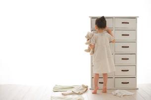 引き出しから捜し物をする女の子の写真素材 [FYI02025504]