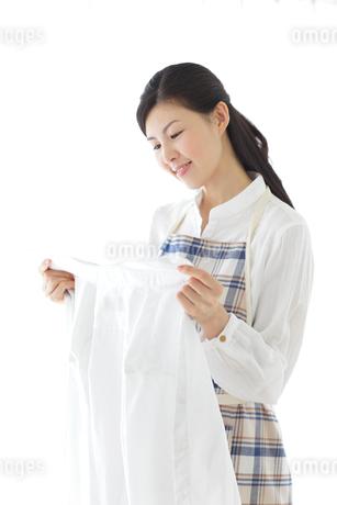 洗濯物を手に持つ若い主婦の写真素材 [FYI02025505]