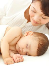 眠る赤ちゃんと見守るお母さんの写真素材 [FYI02025521]