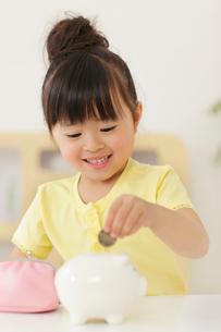 貯金箱にお金を入れる女の子の写真素材 [FYI02025526]