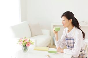 家事の合間にお茶を飲みくつろぐ若い主婦の写真素材 [FYI02025639]