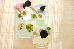 ダイニングテーブルで食事をする家族の俯瞰写真の写真素材 [FYI02025709]