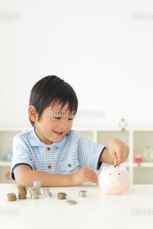 貯金箱にお金を入れる男の子の写真素材 [FYI02025888]